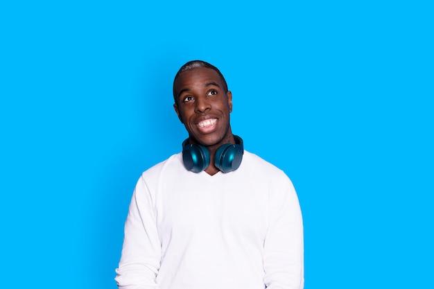 Ein hübscher dunkelhäutiger mann mit kopfhörern um den hals, während er vor blauem hintergrund wegschaut