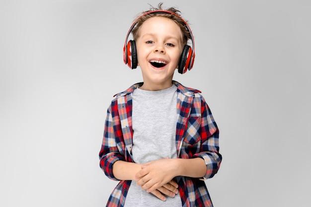 Ein hübscher junge in einem karierten hemd, einem grauen hemd und jeans steht ein grau. ein junge in roten kopfhörern. der junge hält die hände auf den bauch. der junge lacht.