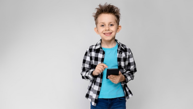 Ein hübscher junge in einem karierten hemd, in einem blauen hemd und in einer jeans steht auf einem grau. der junge hält ein telefon in der hand