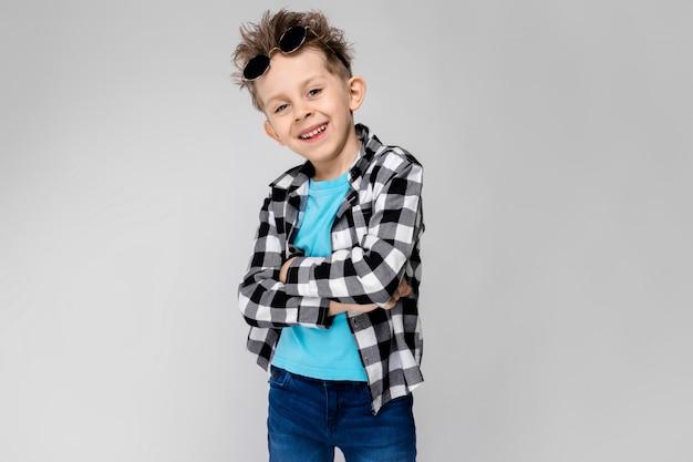Ein hübscher junge in einem karierten hemd, in einem blauen hemd und in jeans steht auf einem grauen hintergrund. der junge trägt eine runde brille. der rothaarige junge hob die brille an die stirn