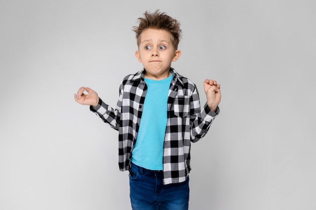 Ein hübscher junge in einem karierten hemd, in einem blauen hemd und in jeans steht auf grau