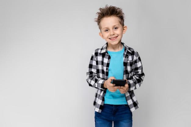 Ein hübscher junge in einem karierten hemd, in einem blauen hemd und in jeans steht. der junge hält ein telefon in der hand