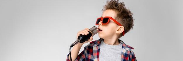 Ein hübscher junge in einem karierten hemd, in einem grauen hemd und in jeans steht auf einem grauen hintergrund. ein junge mit sonnenbrille. der rothaarige junge singt ins mikrofon