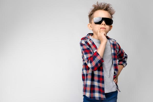 Ein hübscher junge in einem karierten hemd, in einem grauen hemd und in jeans steht auf einer grauen wand.