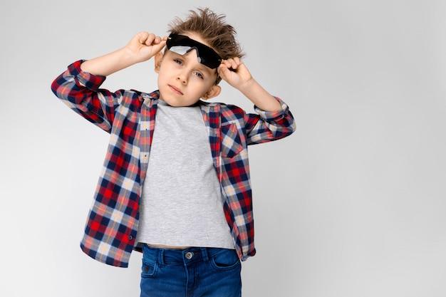 Ein hübscher junge in einem karierten hemd, in einem grauen hemd und in jeans steht. der junge mit der schwarzen sonnenbrille. der junge hält seine brille.
