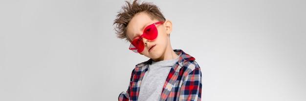 Ein hübscher junge in einem karierten hemd, in einem grauen hemd und in jeans steht. ein junge mit roter sonnenbrille. der junge legte seine hand auf seinen arm.