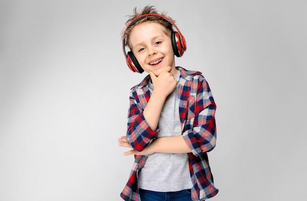 Ein hübscher junge in einem karierten hemd, in einem grauen hemd und in jeans steht