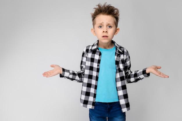 Ein hübscher junge in kariertem hemd, blauem hemd und jeans steht auf grau der junge breitete die hände in beide richtungen aus