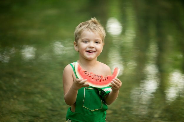 Ein hübscher junge mit einer wassermelone in seinen händen