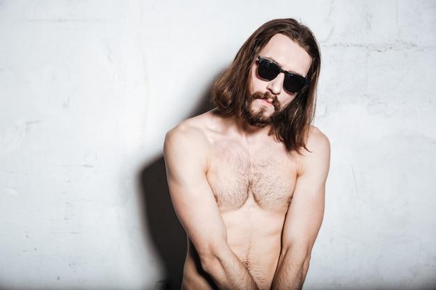 Ein hübscher junger bärtiger hipster-mann mit sonnenbrille, der isoliert über der wand steht?