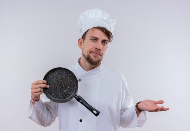 Ein hübscher junger bärtiger kochmann, der weiße kochuniform und hut trägt, die bratpfanne zeigen, während mit überraschtem ausdruck auf einer weißen wand schauen