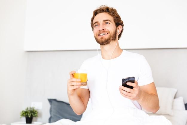 Ein hübscher junger bärtiger mann zu hause, der musik mit kopfhörern unter verwendung des handys hört, der saft trinkt.