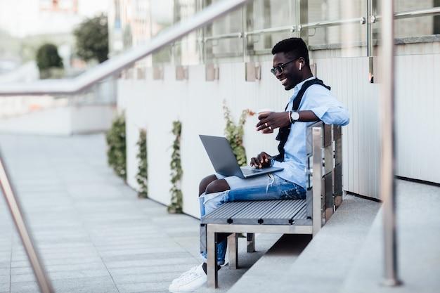 Ein hübscher junger geschäftsmann, der mit seinem laptop auf einer sonnigen straße neben einem park auf einer bank sitzt. mit tasse kaffee.