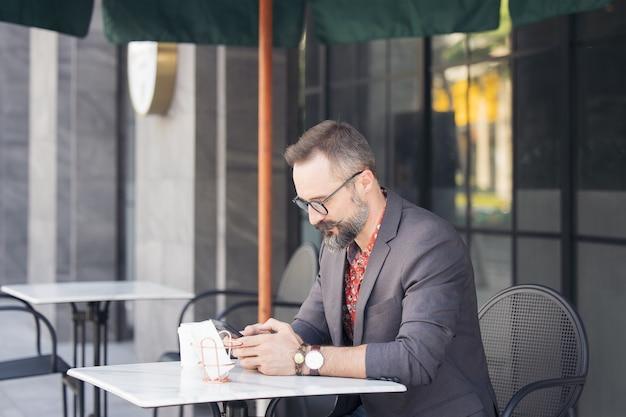 Ein hübscher junger mann auf der terrasse, geschäftsmann, der ein digitales spiel verwendet