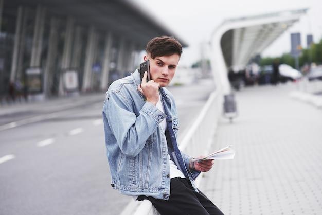 Ein hübscher junger mann, der am telefon nahe dem büroraum spricht.