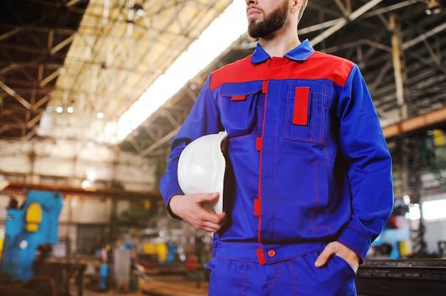 Ein hübscher junger mann - ein arbeiter oder ein ingenieur mit einem weißen bausturzhelm in seinen händen vor dem hintergrund einer anlage oder produktion