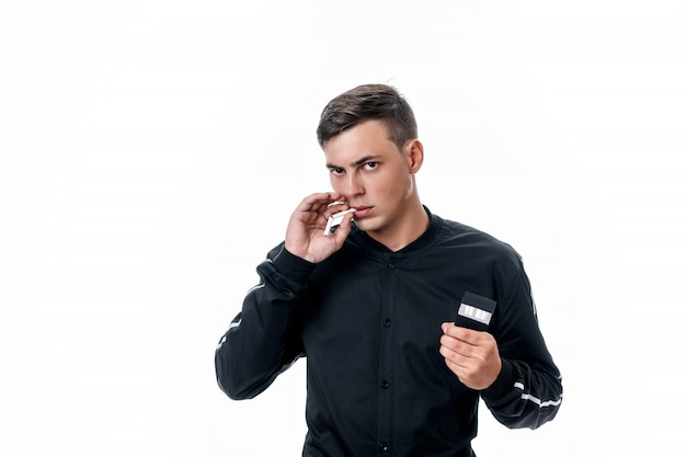 Ein hübscher junger mann hält eine kaputte zigarette im mund, eine packung zigaretten in der anderen hand. mit dem rauchen aufhören. gesundheitsschädlich. schlechte angewohnheiten