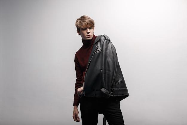 Ein hübscher junger mann in einer stilvollen schwarzen lederjacke im vintage-stil in einem burgunderroten, trendigen golfkleid und trendigen schwarzen jeans steht im studio vor dem hintergrund der wand. moderner gutaussehender kerl. mode