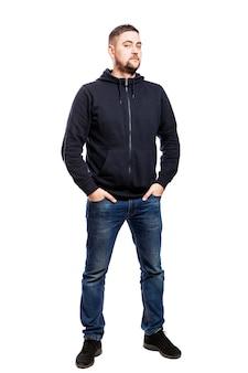 Ein hübscher junger mann in jeans steht. hände in taschen. isoliert weiß vertikale.