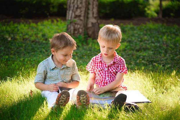 Ein hübscher kleiner junge, der ein buch auf einem grünen gras liest. kinder und wissenschaft. Premium Fotos