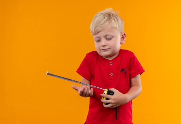 Ein hübscher kleiner junge mit blondem haar, der rotes t-shirt trägt, das maßband zentimeter an einer gelben wand hält