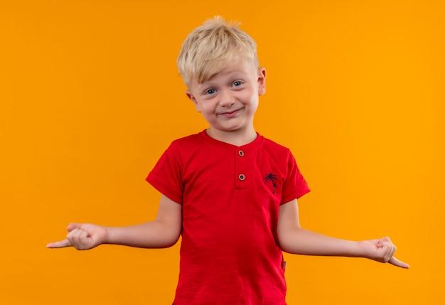 Ein hübscher kleiner junge mit blonden haaren und blauen augen, die rotes t-shirt tragen, das mit zeigefingern zeigt, während auf einer gelben wand schaut