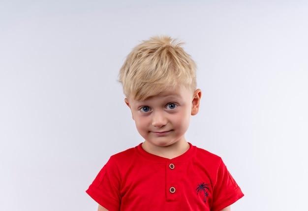Ein hübscher kleiner junge mit blonden haaren und blauen augen, die rotes t-shirt tragen, das überraschend auf einer weißen wand schaut