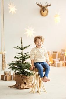 Ein hübscher lockiger kleiner junge sitzt auf einem holzstuhl nahe einem weihnachtsbaum