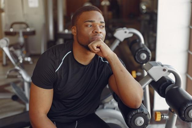 Ein hübscher schwarzer mann ist in einem fitnessstudio beschäftigt