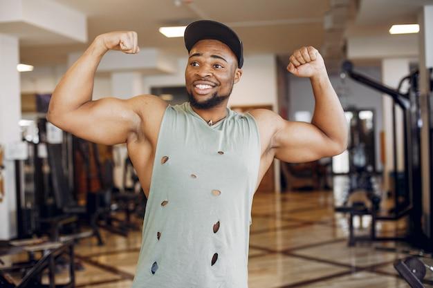 Ein hübscher schwarzer mann nimmt an einer turnhalle teil