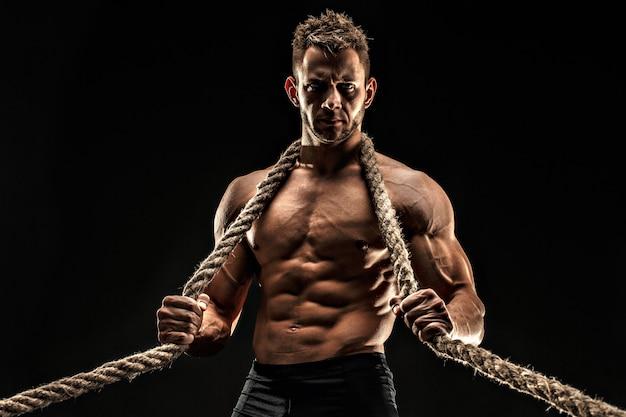 Ein hübscher sexueller starker junger mann mit dem muskulösen körper, der seil hält
