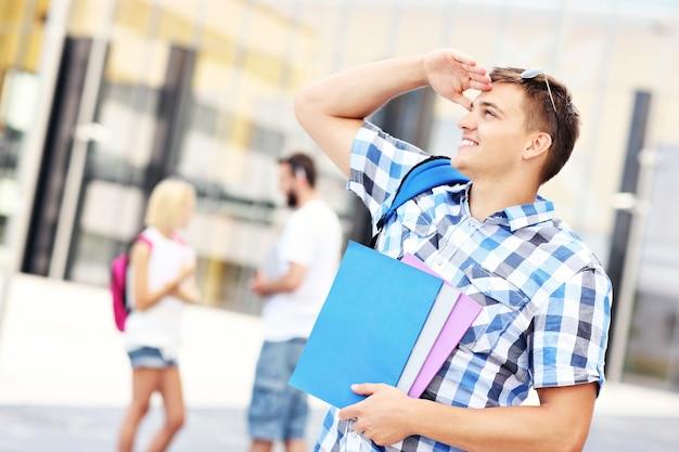 Ein hübscher student, der auf dem campus nach links schaut left
