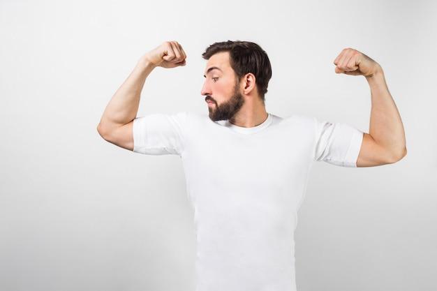 Ein hübscher überzeugter junger mann, der große muskeln auf seinen händen steht und zeigt. er schaut einen von ihnen an und ist sehr stolz auf sie. er trägt ein weißes t-shirt, lokalisiert auf weißer wand.