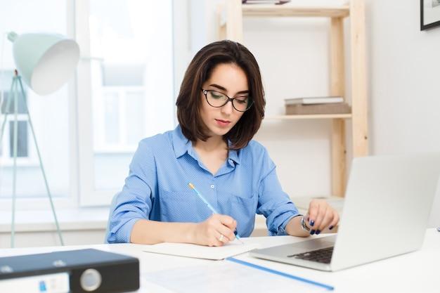 Ein hübsches brünettes mädchen arbeitet am tisch im büro. sie trägt ein blaues hemd und eine schwarze brille. sie schreibt ernst.