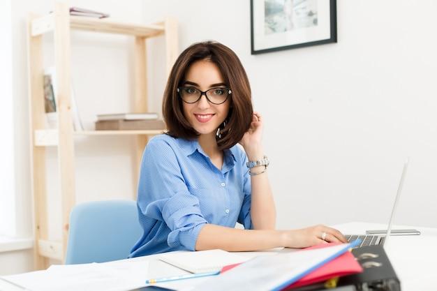 Ein hübsches brünettes mädchen in einem blauen hemd sitzt am tisch im büro. sie arbeitet mit einem laptop und lächelt süß in die kamera.