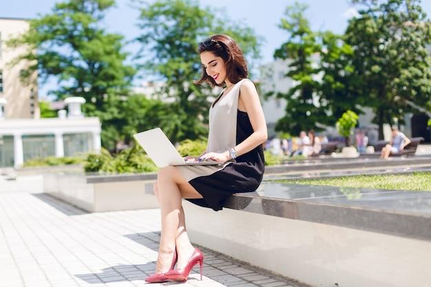 Ein hübsches brünettes mädchen in grauem und schwarzem kleid und weinigen absätzen sitzt im park in der stadt. sie tippt auf einem laptop und sieht glücklich aus, draußen zu arbeiten.