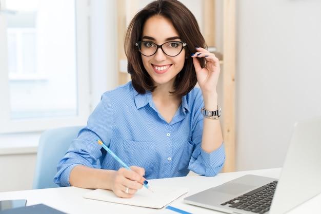 Ein hübsches brünettes mädchen sitzt am tisch im büro. sie trägt ein blaues hemd und eine schwarze brille. sie schreibt und lächelt in die kamera.