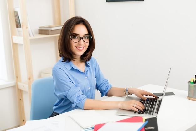 Ein hübsches brünettes mädchen sitzt und tippt auf einem laptop am tisch im büro. sie lächelt freundlich in die kamera. sie trägt ein blaues hemd und eine schwarze brille.