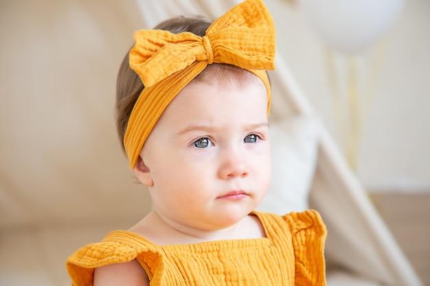 Ein hübsches einjähriges kaukasisches mädchen in gelben kleidern sitzt auf dem boden und schaut weg. studiofoto zum geburtstag eines kindes.