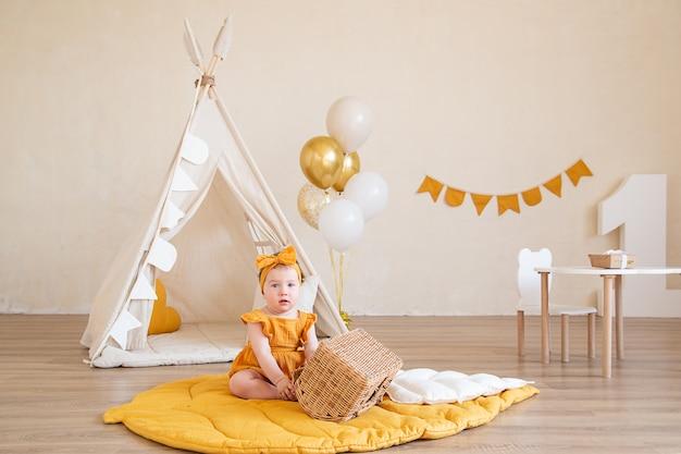 Ein hübsches einjähriges mädchen in gelben kleidern sitzt auf dem boden und spielt mit einem korb. studiofoto zum geburtstag eines kindes.