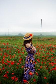 Ein hübsches junges mädchen steht in einem kleid mit offenen schultern und einem strohhut in einem schönen mohnfeld. nahansicht.