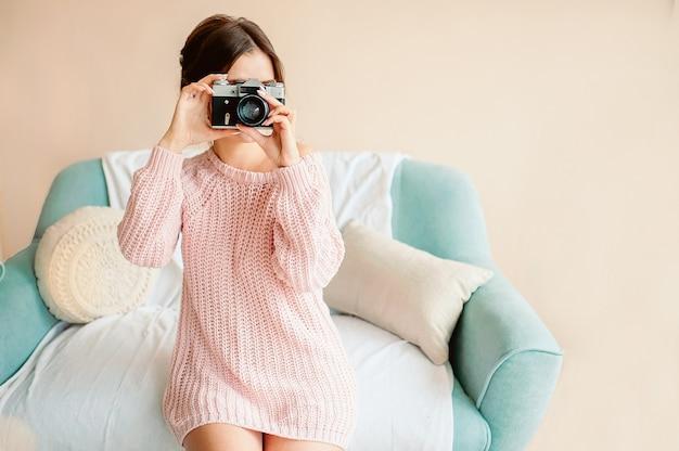 Ein hübsches junges mädchen von europäischem aussehen hält eine vintage-kamera in einem gemütlichen haus in der hand