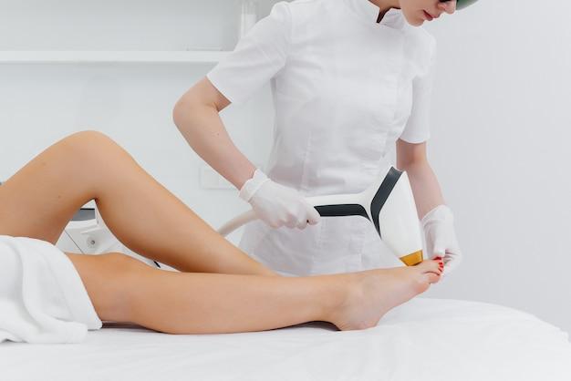 Ein hübsches junges mädchen wird in einem spa-salon mit modernen geräten einer laser-haarentfernung unterzogen. schönheitssalon. körperpflege.