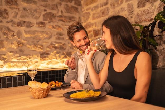Ein hübsches junges paar verliebt in ein restaurant, spaß beim gemeinsamen abendessen haben, valentinstag feiern