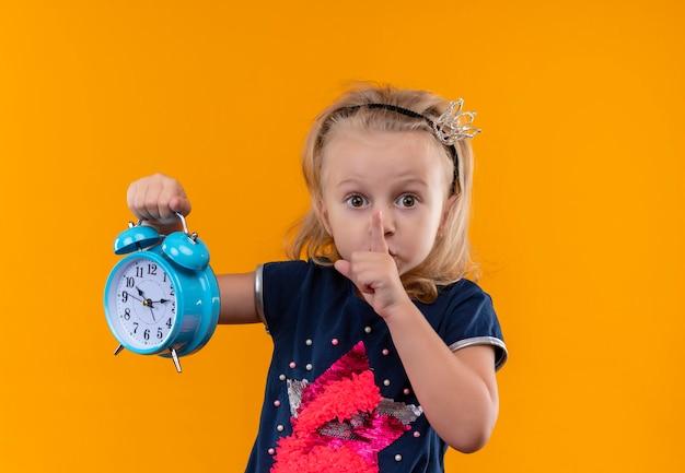 Ein hübsches kleines mädchen, das ein dunkelblaues hemd im kronenstirnband trägt, das shh geste zeigt, während blauer wecker auf einer orange wand hält