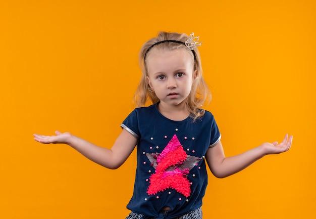 Ein hübsches kleines mädchen, das ein dunkelblaues hemd im kronenstirnband trägt, das überraschend mit offenen armen auf einer orange wand sieht