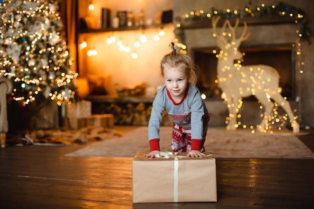 Ein hübsches kleines mädchen im traditionellen schlafanzug erhielt ein weihnachtsgeschenk