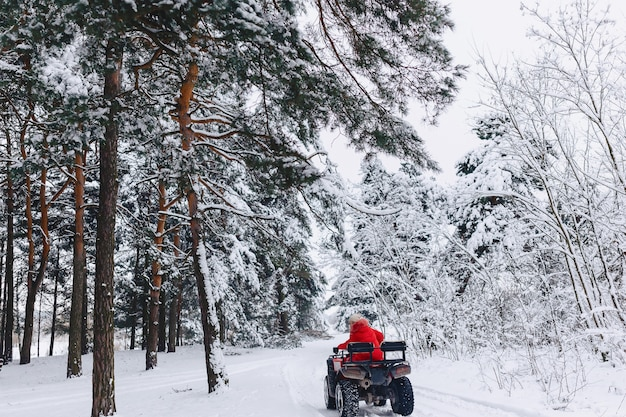 Ein hübsches mädchen, das ein quadrocycle in einem malerischen schneebedeckten bereich reitet