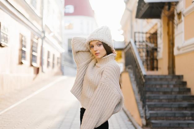 Ein hübsches mädchen in einem warmen pullover und hut geht durch die herbststadt