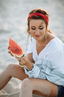 Ein hübsches mädchen in jeans, kurzen shorts, einem roten reifen und einem weißen bh sitzt im sand